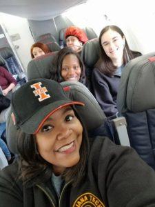 Lisa Givan selfie with spring break crew behind her on the plane